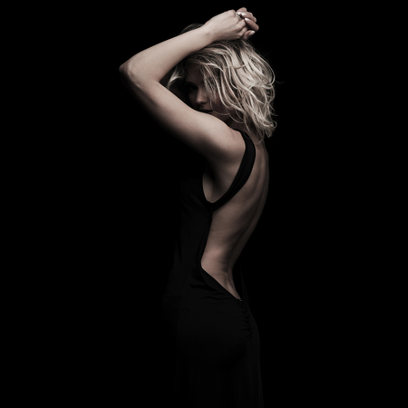 portrait of seductive blonde woman wearing a backless dress posing with hands above head while standing on black background