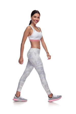 smiling sexy woman walking to side in gym clothes on white background. She is wearing a pair of white leggings and a white top Stock Photo