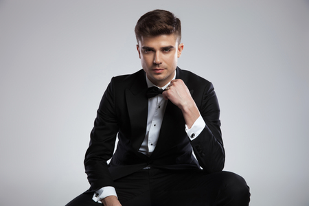 portrait of seated young businessman in tuxedo fixing his black bowtie on light grey background