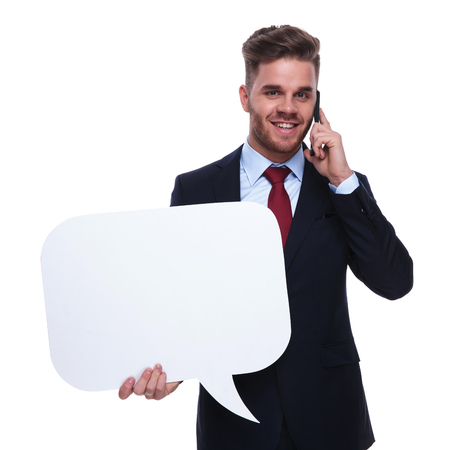 young handsome businessman with speech bubble talks on the phone while standing on white background