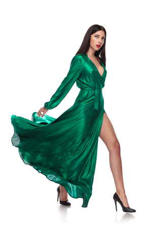 woman in flying long green dress steps to side on white background, full length picture