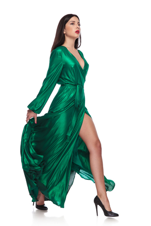 sensual woman in fluttering long green dress walks to side while holding it, on white background, full body picture
