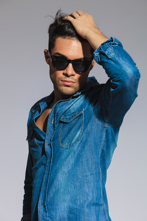 portrait of sexy casual man in denim shirt with glasses fixing his hair while standing on light grey background