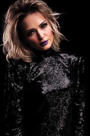 portrait of beautiful woman in black gleaming dress with purple lipstick leaning her head to side while standing on black background