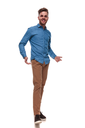 happy casual man wearing a blue shirt standing on white background and presenting, full length picture