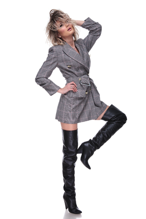 woman with grey jacket with checkers fixing her hair while standing on white background with raised leg, full body picture