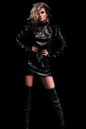 beautiful blonde woman wearing black shiny dress and long leather boots holding her hips while standing on black background, full length picture
