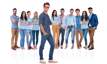 young casual man with glasses and hand in pocket presenting his team standing behind on white background Stock Photo