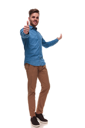 handsome casual man makes ok sign and presents behind while standing on white background, full length picture