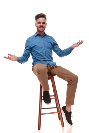 seated young casual man making a welcoming gesture with both hands on white background Stock Photo