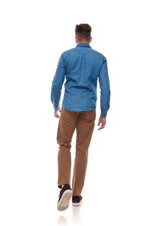 back view of young man in casual clothes walking on white background, full length picture