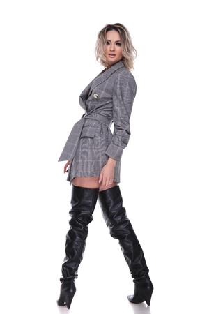 Vista posterior de la mujer en traje mirando hacia atrás mientras está de pie sobre fondo blanco.