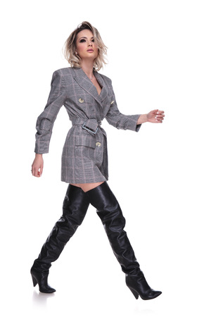 side view of attractive woman wearing grey plaid suit and black leather boots walking to side and looking up on white background, full body picture