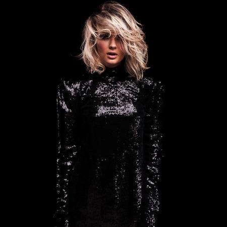 portrait of sensual blonde woman wearing black shiny dress standing on black background, looking shocked