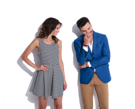woman is looking at his man while they both laugh. They are standong on white background, and the man is covering his mouth, looking embarrased