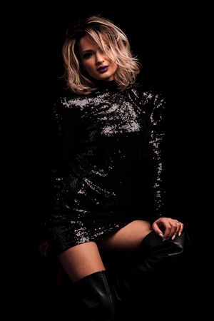 seductive woman in glistening black dress and leather boots sitting on a wooden stoll on black background