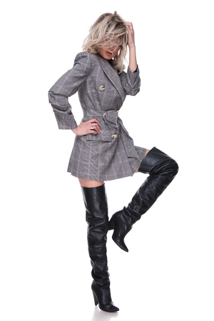 woman wearing grey suit and black leather boots fixing her messy hair while standing on white background with a leg up, full body picture