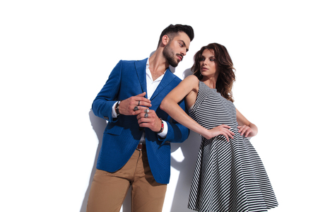 sexy woman leaning on his man and looking at him while standing on white background together, bottom angle picture Banco de Imagens