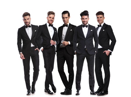 five handsome men in black tuxedoes standing together on white background, full body picture Stock Photo