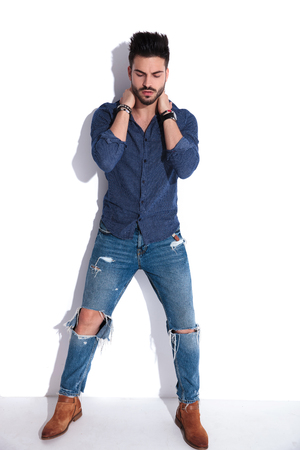 man in navy shirt and ripped jeans posing while holding his neck with both hands. and looking down. He is standing near a white wall, full body picture
