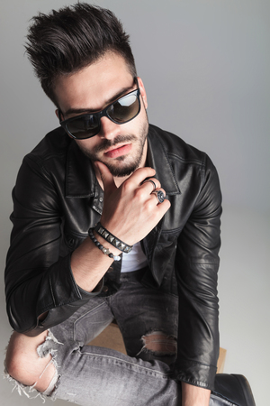 portrait of sexy man with sunglasses thinking while sitting on a wooden box on light grey background. He is wearing a leather jacket and a pair of grey ripped jeans