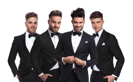 four young men in black tuxedoes standing together on white background with hands in pockets, one of them buttoning his suit, portrait picture