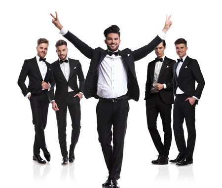 groom makes victory sign in front of his team while standing on white background, dressed in black tuxedo