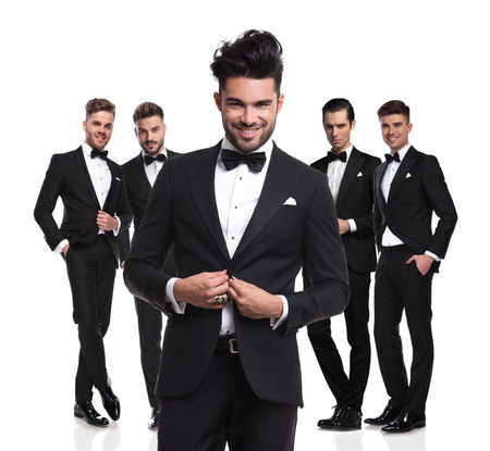 five attractive elegant men standing on white background with leader buttoning his suit in front