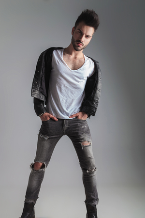 sexy man in leather jacket and grey jeans stands on light grey background with hands in pockets, looking seductive, full body picture