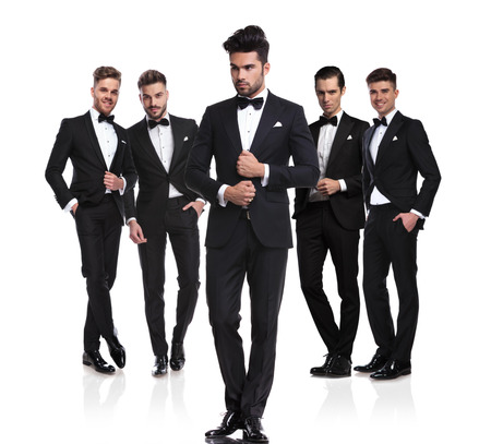 leader of young groomsmen holds suit collar and looks to side while standing on white background in front of them