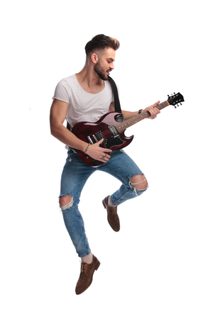 young rock star jumping while playing the guitar during a concert on white background Stock Photo