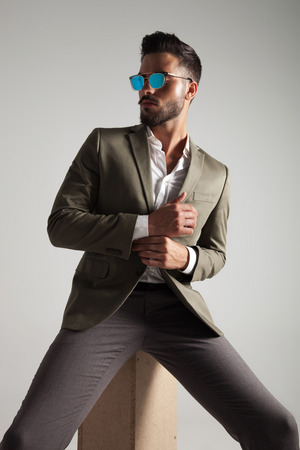stylish man with green suit and sunglasses arranges his cuffs and looks to side while sitting on a wooden box on light grey background