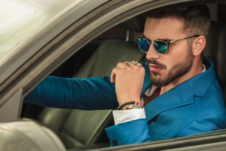 smart casual man with sunglasses and blue suit driving his grey car, portrait picture 版權商用圖片