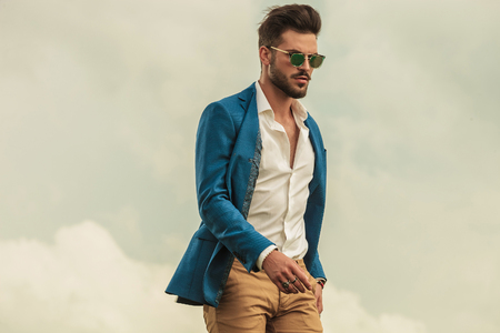 smart casual man with sunglasses standing on grey clouds background and looking down to side 写真素材