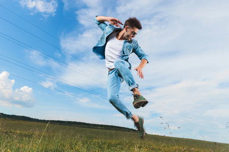 casual man with sunglasses leaping from the ground while looking down, outdoor picture
