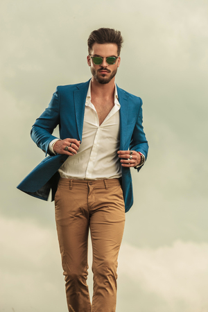 sexy man holding blue suit collar and wearing sunglasses walking on clouds background, Stock Photo
