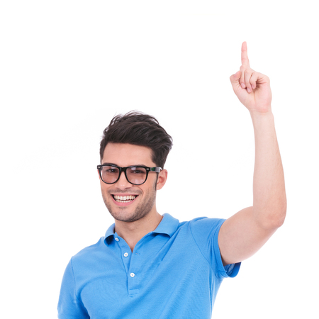 smiling young casual man pointing up at something on white background