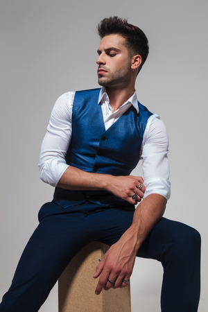portrait of sexy seated man in blue vest looking down to side while fixing his sleeve on light grey background