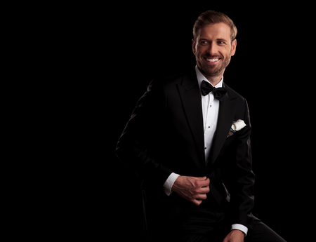 side view of a laughing elegant man in tuxedo holding button on black background Stock Photo