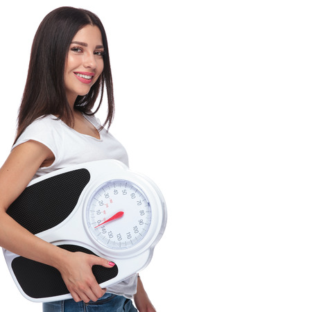 side view of happy woman promoting a healthy lifestyle while holding a scale in her hand, on white background