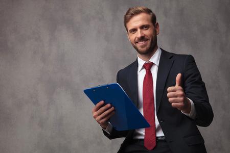 lächelnder junger Geschäftsmann, der eine Zwischenablage hält, macht das OK-Zeichen auf Studiohintergrund