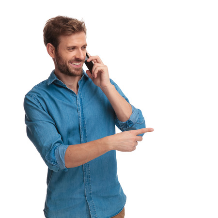 smiling casual man talking on the phone points finger to side at something on white background Banque d'images