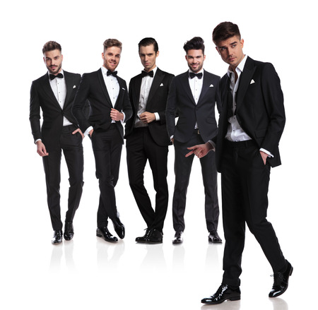 team of five grooms with leader snapping fingers and walking in front on white background, full length picture Stock Photo