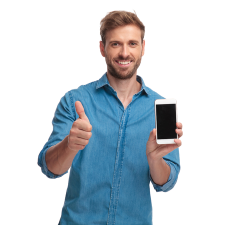 smiling casual man showing the blank screen of his phone and makes the ok sign on white background