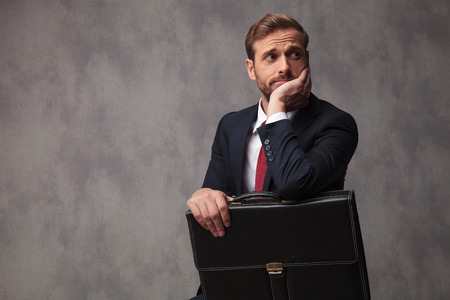 insecure businessman looks worried and pensive with chind in his palm, holding his suitcase and looks to side on studio background Stok Fotoğraf