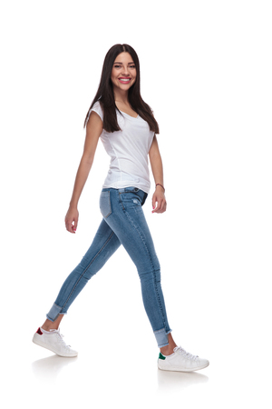 side view of cute casual woman in jeans walking on white background, full length picture