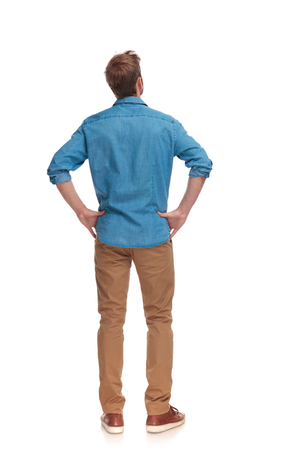 back view of a casual man with hands on waist standing and looking up on white background Фото со стока