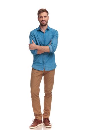Confiant homme décontracté souriant avec les mains croisées dans une pose de corps entier