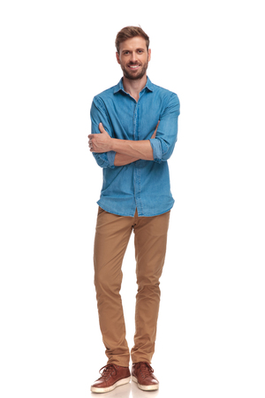 confident smiling casual man with hands crossed in a full body pose on white background Archivio Fotografico - 107380531