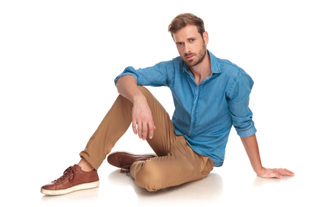young casual man relaxing on the floor on white background Foto de archivo - 107380545